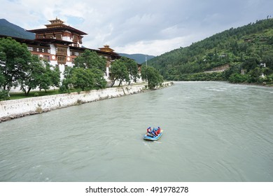 A group of adventurers travels through a river in front of the Punakha Dzong using an Inflatable boat in the evening with cloudy sky.