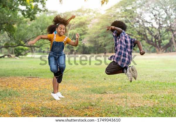 Group of African American children having fun jumping over the rope in the park. Education or Field trip concept