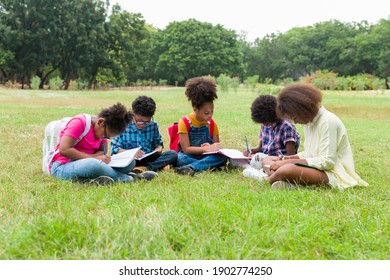 Group of African American children learning and writing book in the park. Diversity black people learning outside the classroom. Kids field trips outside. Kids and educational concept
