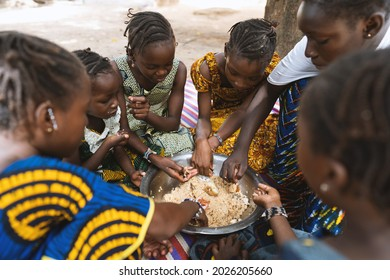 Group of African girls sitting around a big plate with rice and vegetables, enjoying their meal
