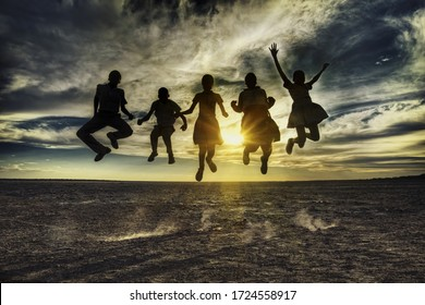 Group of african kids jumping in the sunset, Botswana