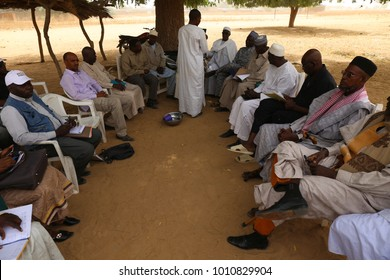Group of african men and women sitting on chairs and talking together. Outdoor view in the place of a rural village in Chad called Dourbali. People discussing. Picture taken on 2nd february 2017.