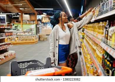 Group of african womans buying sunflower oil bottle in supermarket.