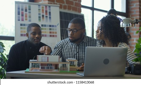 Group of African-American men and woman coworking on design of hi-tech living house with alternative energy resources in use