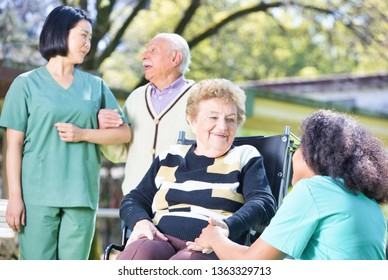 Group of aged senior people and multi ethnic nurses on the garden talking and smiling.