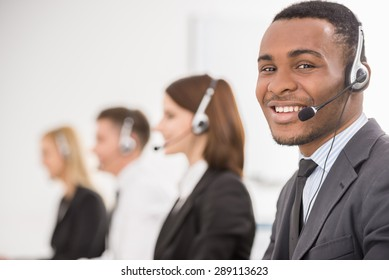 Group of agents sitting in line in a bright call centre.