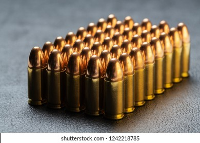 Group of aligned 9 mm bullets for handgun isolated on dark background viewed from side. Gun control, crime, military-industrial complex or defense concepts.