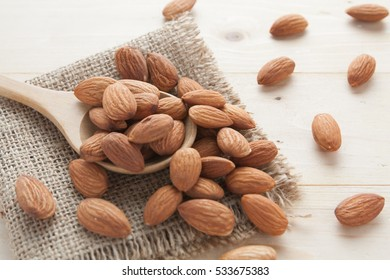 group of almonds  from wood spoon on wood background