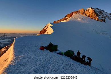 group alpinists in base camp on snowy peak places tent at sunset, Fann, Pamir Alay, Tajikistan