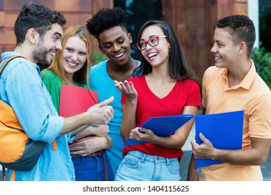 Group of american and latin and african students talking about homework outdoors in summer