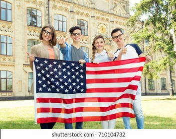 Group of American students holding flag of USA on the university campus. Group four happy people having waving American flag. International language learn course.