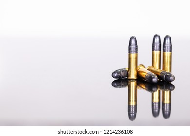 group of ammunition on a table with reflections, white background