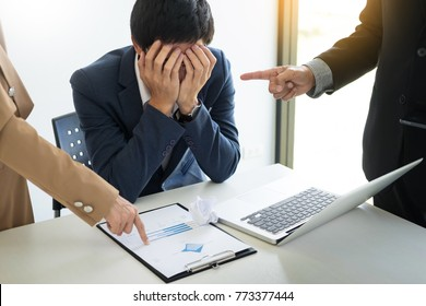 Group Of Angry Business people Blaming Male Colleague In Meeting for business mistake in office
