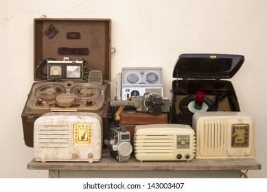 A group of antique gadgets on an old table. Three tube radios, two movie cameras, a record player, two reel-to-reel tape players with microphones and a cartridge tape player.