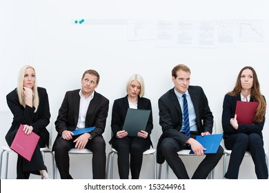 Group of applicants for a vacant post or corporate job sitting in a long line with folders containing their credentials carefully ignoring each other