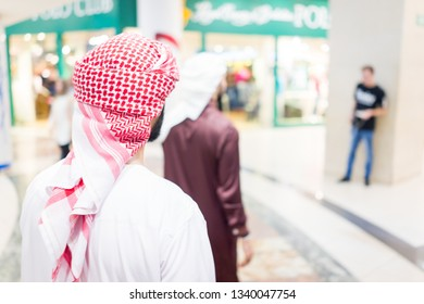 Group of Arab men walking together in mall