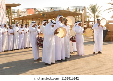 Group of Arab men in white kandura performing traditional dances and singing while beating drums during Sheikh Zayed Heritage Festival in Al Wathba, United Arab Emirates-  January 20th, 2018.
