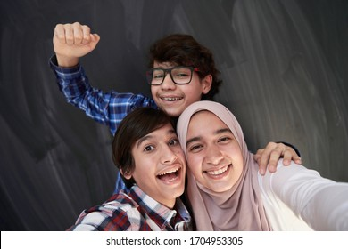 group of arab teens taking selfie photo on smart phone with black chalkboard in background