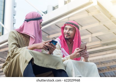 The group of arabian businessman smiling and watching a smartphone