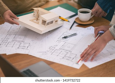 Group of an architect working and measuring scale of a mass model on table in office