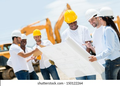 Group of architects at a construction site looking at blueprints