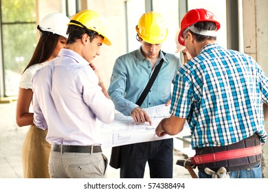 Group of architects and experts discuss about construction project.Looking blueprint of new project.