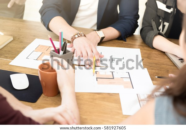 Group of architects (or interior designers) discussing floor plans in the meeting