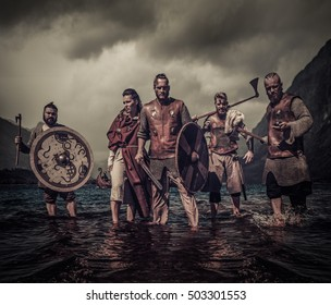A group of armed Vikings, standing on river shore.