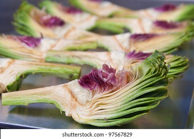 group of artichokes cut on a sheet pan