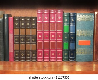 Group of artificial leather bound books, on a shelf