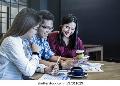 Group Of Asian Business people with casual suit Meeting in looking at the smart phone action In the modern coffee shop, business group concept