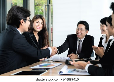 Group of Asian business people meeting at outdoor cafe. Businessmen shaking hands during a meeting