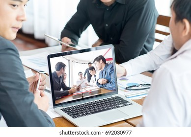 Group of asian Business team attending video conference discussion sitting desk in office monitor with another group
