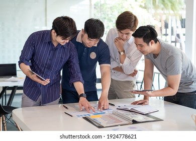 Group of Asian businessman brainstorm their work ideas using a tablet, taking note pointing at a graph at the office.