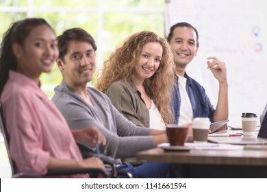 Group of Asian and caucasian businessmen is meeting his work. And happily smile at their job. In the modern office. There is flip shart board behind.