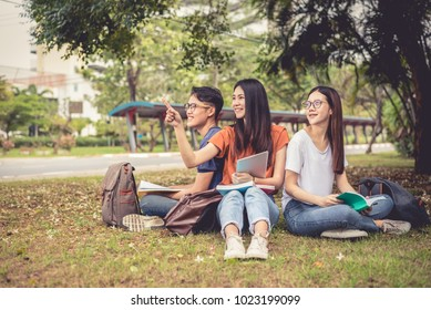 Group of Asian college student reading books and tutoring special class for exam on grass field at outdoors. Happiness and Education learning concept. Back to school concept. Teen and people theme.