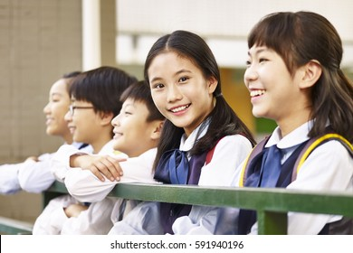 group of asian elementary school children with one schoolgirl looking at camera smiling.