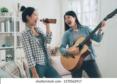 Group of asian female friends playing karaoke at home. Concept about friendship home entertainment young people. two girl roommates love music happy relax dancing singing with bottle of beer.