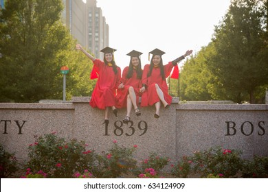 Group of Asian Female Graduates in Red Graduation Gown Sitting on University's Engraved Stone Sign