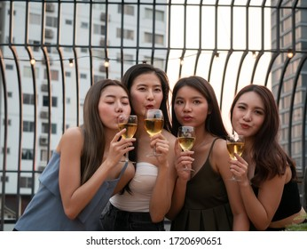 Group of asian friend cheering and drinking at terrace party. Young people toasting glass with wine at rooftop restaurant. Friendship ,youth lifestyle and nightlife concept.