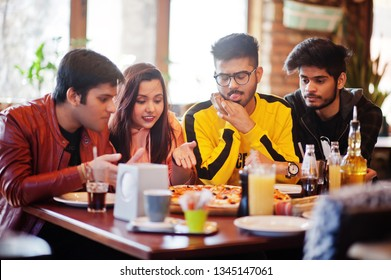 Group of asian friends eating pizza during party at pizzeria. Happy indian people having fun together, eating italian food and sitting on couch.