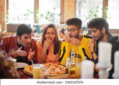 Group of asian friends eating pizza during party at pizzeria. Happy indian people having fun together, eating italian food and sitting on couch. Shocked and surprise faces.