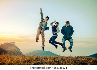 Group of asian friends having fun jumps on sunset and mountains with filter effect