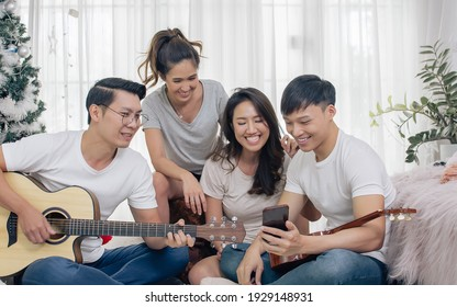 Group of asian friends having party, playing guitar and singing together with fun at home. Lifestyle Concept.