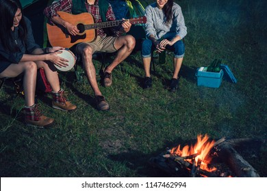 A  group of Asian friends sitting on chairs, singing, playing a guitar and drinking some beer and water together outside the tent near the fire while they has camping on Weekend holiday.