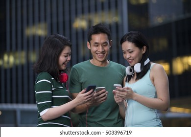 Group of Asian friends using mobile phone's outside in city at night.