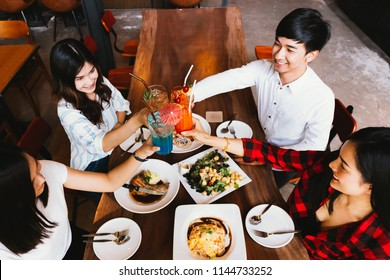 Group of Asian happy and smiling young man and women holding an alcoholic cocktail for toasting and celebrating in social party in restaurant - top view