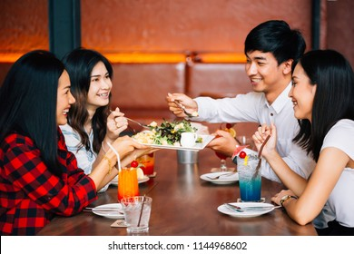 Group of Asian happy and smiling young man and women having a meal together with enjoyment and happiness