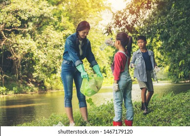 Group of asian kids and teacher school volunteer charity environment under tree near river water. volunteer charity to green recycling bag cleaning park together at ratchaburi thailand.