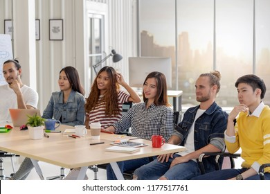 Group of Asian and Multiethnic Business member team with casual suit in listening the senior manager giving the speech in front of the modern workplace, diversity concept